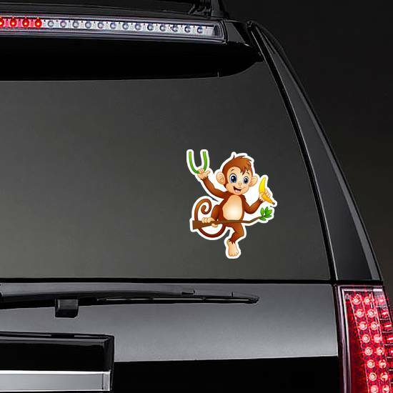 Cartoon Monkey On A Tree Branch Holding Banana Sticker on a Rear Car Window example