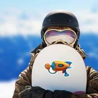 Cartoon Retro Space Blaster Handgun Sticker on a Snowboard example